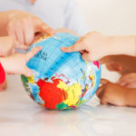 Multicultural childrens hands on a globe